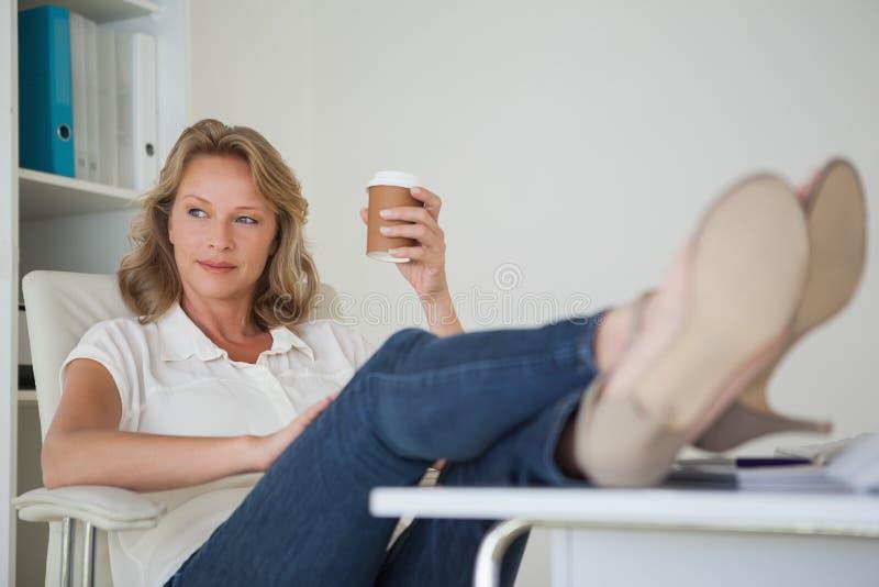 Toevallige onderneemster die een koffie met haar voeten heeft omhoog bij bureau stock foto