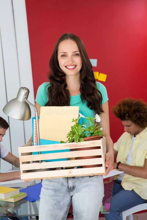 Toevallige onderneemster die haar bezittingen in doos dragen stock fotografie