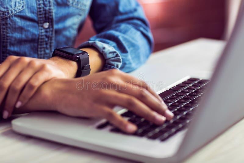 Toevallige onderneemster die laptop met behulp van en smartwatch royalty-vrije stock afbeeldingen