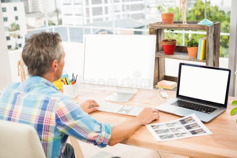 Toevallige ontwerper die aan computer werken stock afbeelding