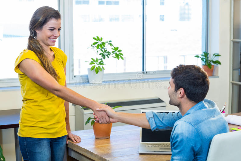 Toevallige partners die hun handen schudden stock foto's