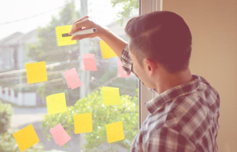 Toevallige Start bedrijfsmens die op markeringsdocument schrijven op vensters stock afbeeldingen