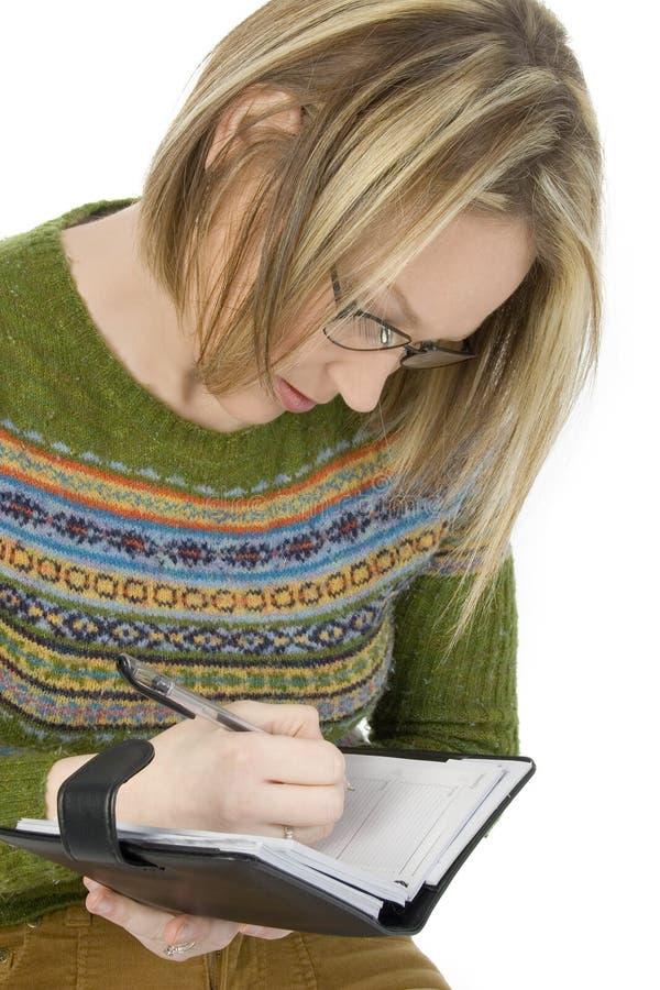 Toevallige Vrouw die in Datebook schrijft stock afbeelding
