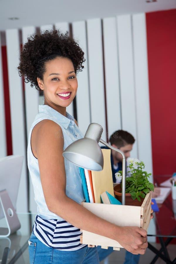 Toevallige vrouw die haar bezittingen in doos dragen stock foto