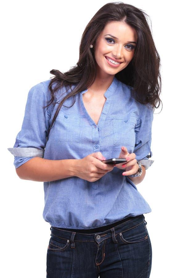 Toevallige vrouw met een telefoon in haar hand stock fotografie
