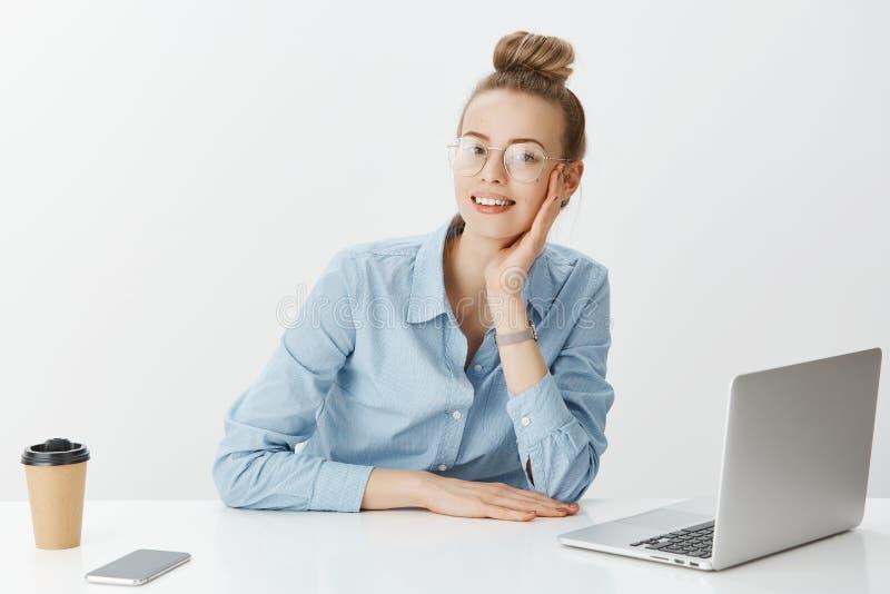 Toevallige werkdag in bureau Portret die van positieve knappe onderneemster in glazen, dichtbij laptop smartphone zitten royalty-vrije stock fotografie