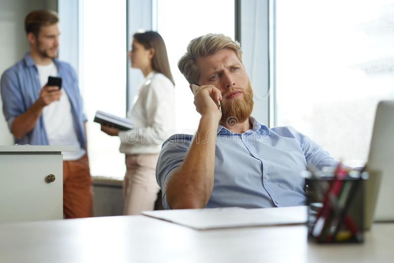 Toevallige zakenman die bij bureau werken, die mobiele telefoon en laptop met behulp van royalty-vrije stock foto