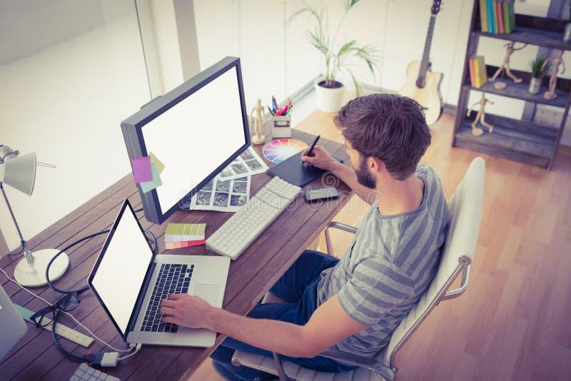 Toevallige zakenman die computers in bureau met behulp van royalty-vrije stock foto's