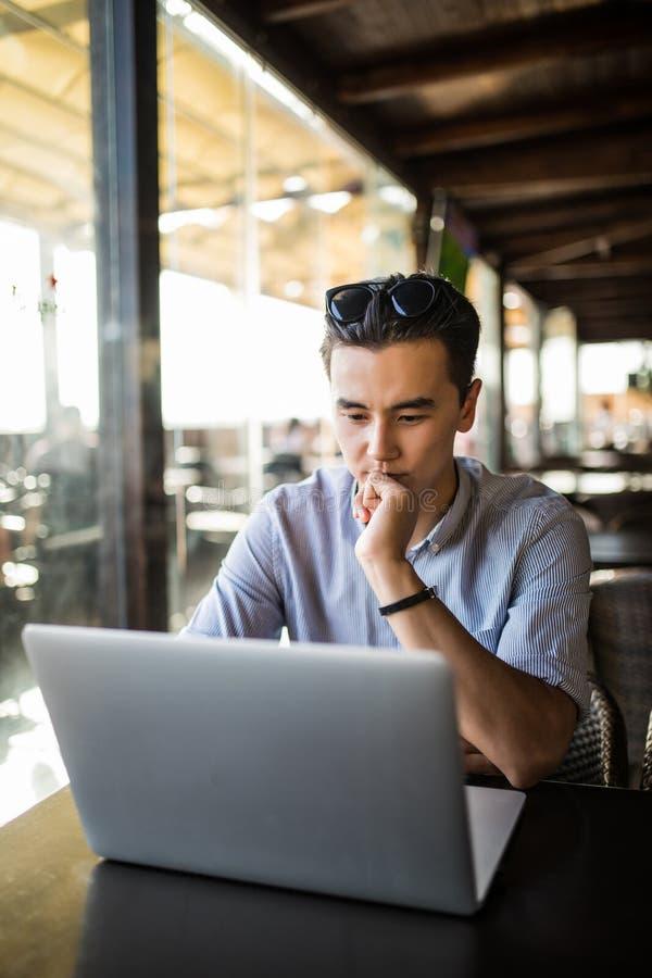 Toevallige zakenman die met laptop in koffie jonge Aziatische ondernemer werken die over project denken Het freelance werk stock foto