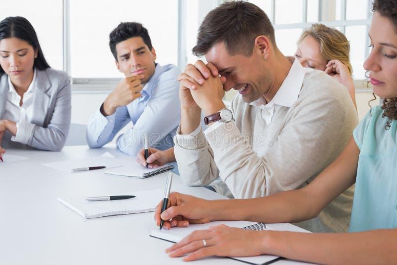 Toevallige zakenman die niet tijdens vergadering proberen te lachen stock afbeeldingen