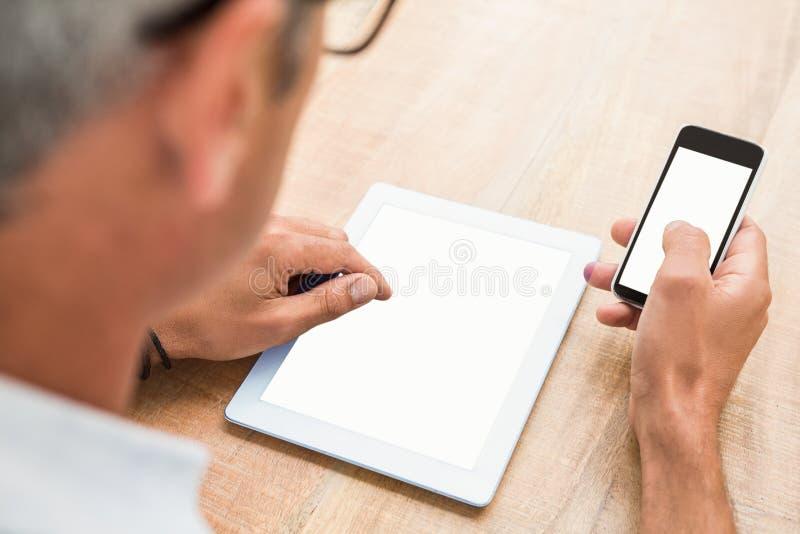 Toevallige zakenman die smartphone en tablet gebruiken royalty-vrije stock foto's