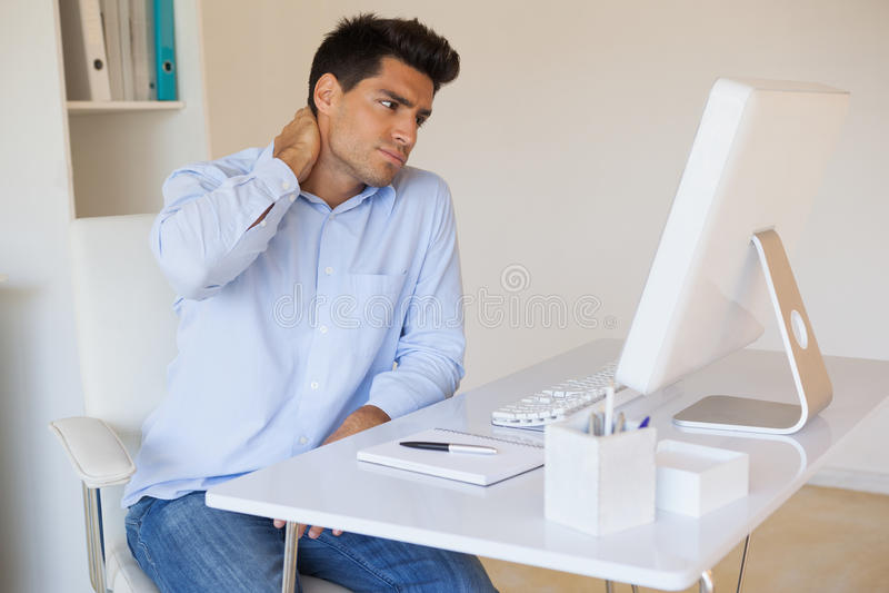 Toevallige zakenman wat betreft zijn pijnlijke hals stock foto