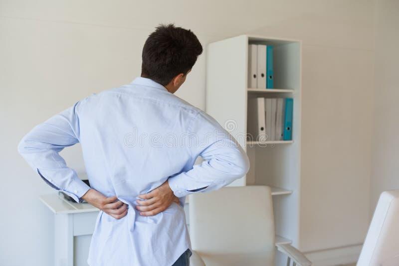 Toevallige zakenman wat betreft zijn pijnlijke rug stock foto's