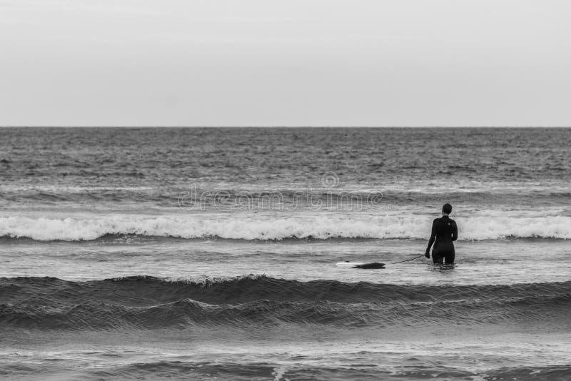 TOFINO, KANADA - 2. September 2018: Surfer- oder Wellenreiter, der das Surfbrett auf dem Hintergrund von Ozean hält stockfoto
