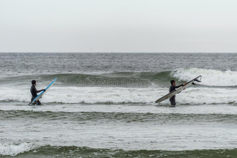 TOFINO, KANADA - 2. September 2018: Surfer- oder Wellenreiter, der das Surfbrett auf dem Hintergrund von Ozean hält lizenzfreies stockfoto