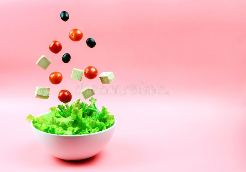 Tofu cheese, cherry tomatoes and olives flying out of the white bowl on a pink background. Concept of a healthy diet. stock photos
