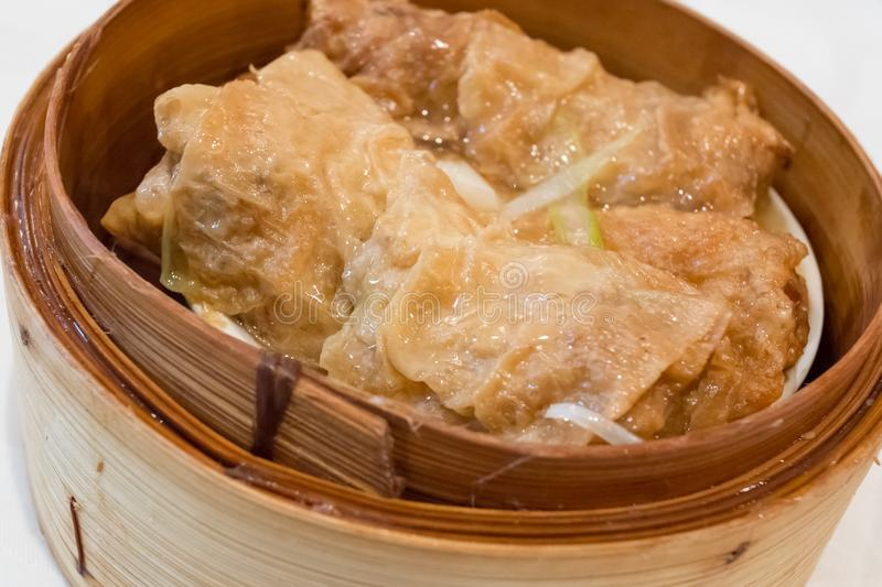 Tofu Skin Rolls. On a small plate inside a steam bamboo basket.  It`s a famous Chinese dim sum dish with meat filling and vegetable like  bamboo shoots wrapped royalty free stock photo
