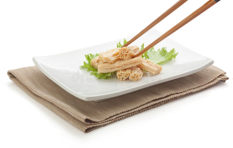 Tofu skin. Some pieces of tofu skin with fresh green lettuce and chopstick on the white plate stock images