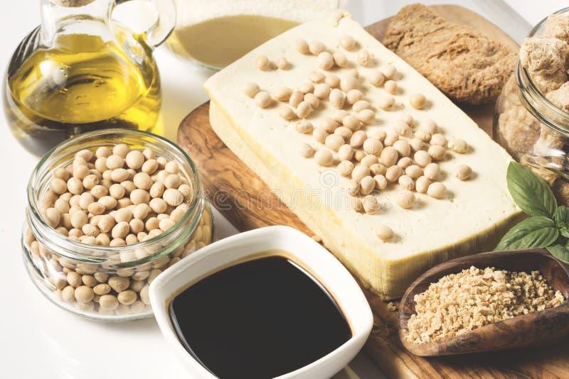 Tofu, Sojamilch, Sojabohnen, Sojaso?e und Sojabohnen?lsahne auf dunklem Schwarzem und Grauhintergrund stockfotografie