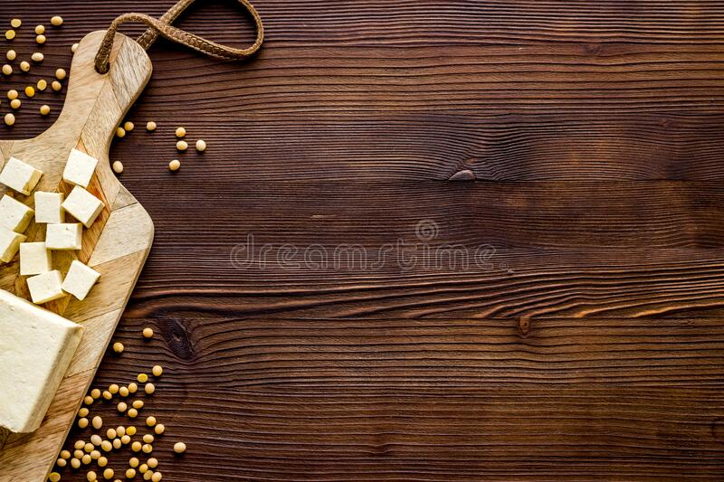 Tofu vegan food on cutting board on wooden table top view copy space stock image