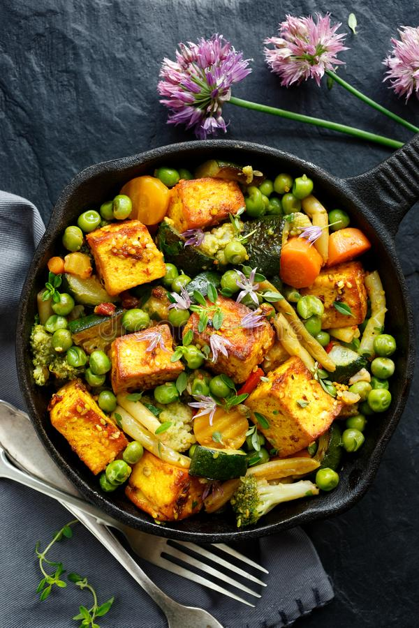 Tofu with vegetables sprinkled with herbs and edible flowers, top view. Vegan dish delicious and nutritious. royalty free stock images