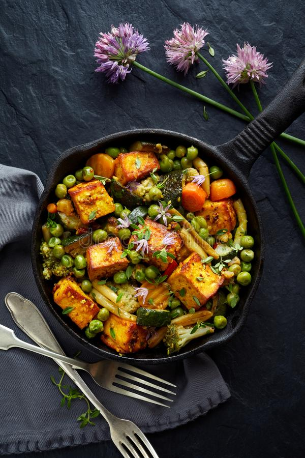 Tofu with vegetables sprinkled with herbs and edible flowers, top view. Vegan dish delicious and nutritious. Healthy eating concept royalty free stock photos