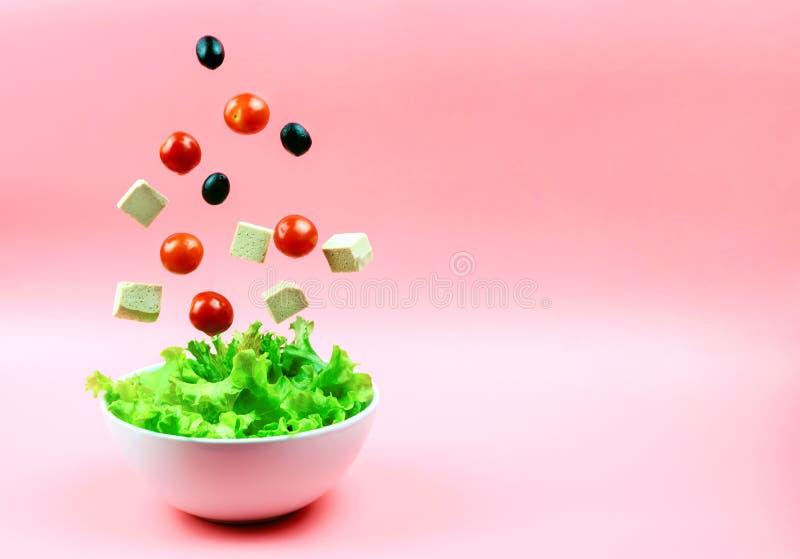 Tofuost, körsbärsröda tomater och oliv som flyger ut ur den vita bunken på en rosa bakgrund Begreppet av ett sunt bantar arkivfoton
