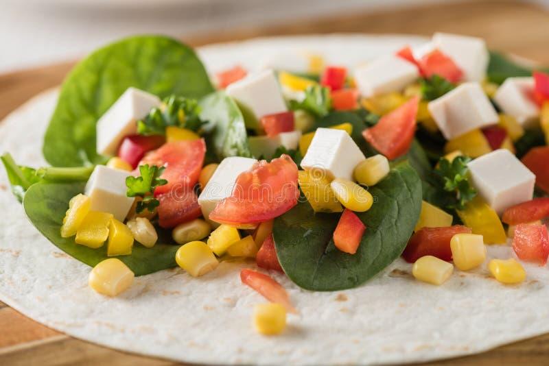 Tofuverpackungen des strengen Vegetariers mit Pfeffer, Mais, Tomaten und Spinat lizenzfreies stockfoto