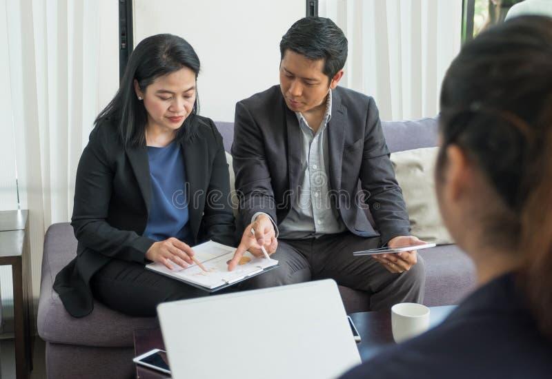 Togerther de trabalho asiático do homem de negócios e da mulher de negócios no escritório, fotos de stock royalty free