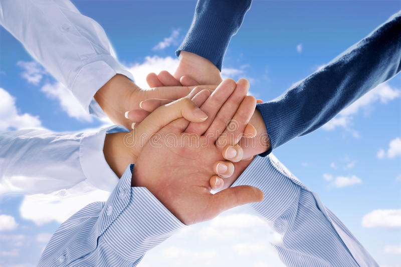 Together. Close up view of hands getting together on blue background royalty free stock photos