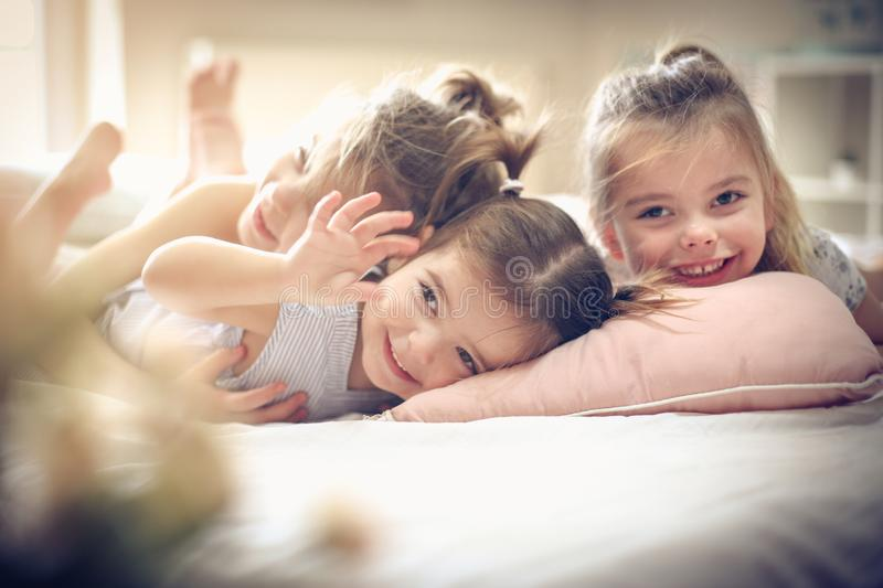 Together in bed. Three little girls lying on bed. Space for copy royalty free stock photography