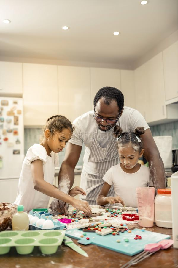Beautiful daughters with nice hairstyles cooking together with father. Together with father. Beautiful cute little daughters with nice hairstyles cooking royalty free stock images