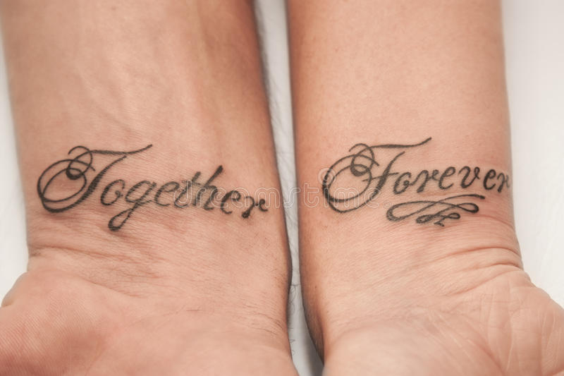 Together forever. Tattoo the word together forever on the male and female hand royalty free stock photos