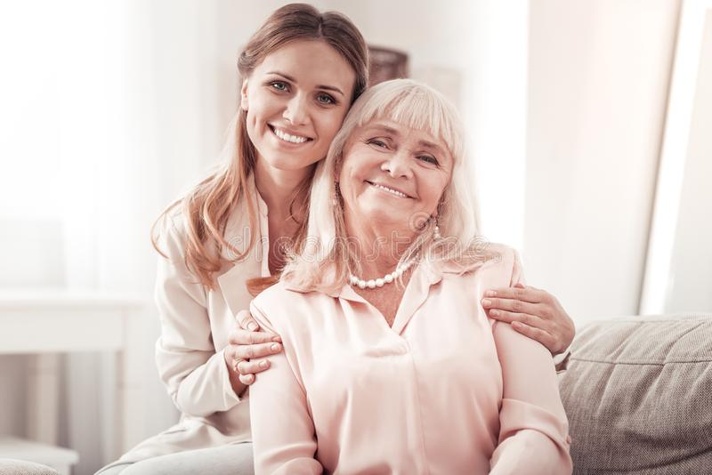 Happy mother and daughter posing to the camera royalty free stock images