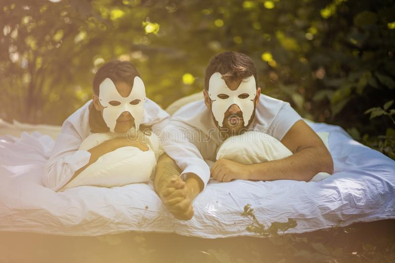 Together with hidden face. Couple in nature with face mask. stock photos