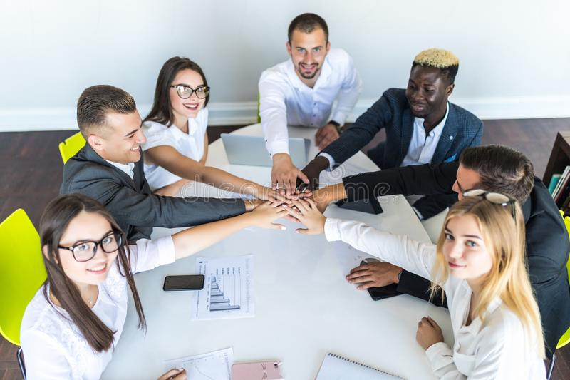 Together we are stronge. Group of happy business people holding hands together while sitting around the desk royalty free stock image