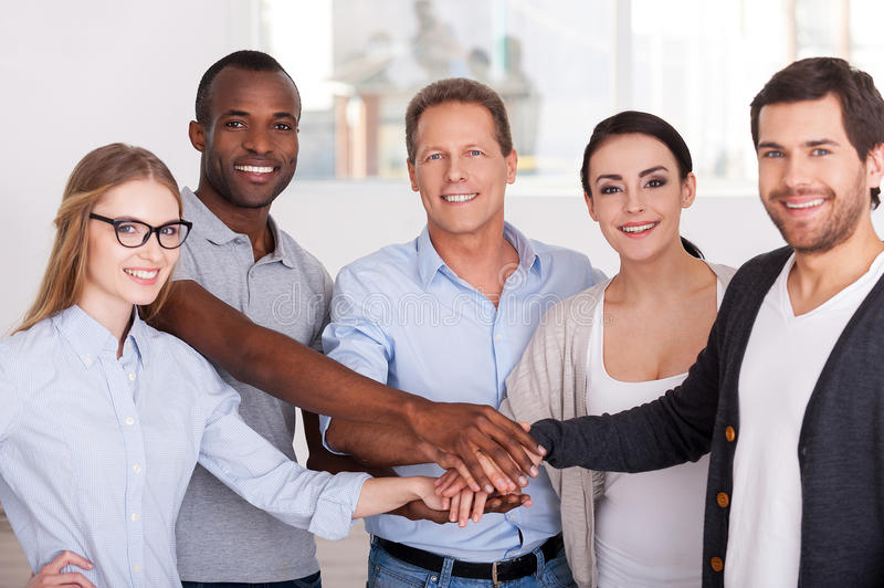 Together we are stronger!. Group of cheerful business people in casual wear standing close to each other and holding hands together royalty free stock image