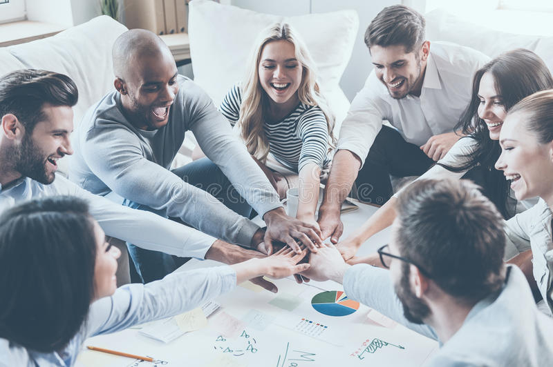 Together we are stronger!. Group of happy business people holding hands together while sitting around the desk royalty free stock image