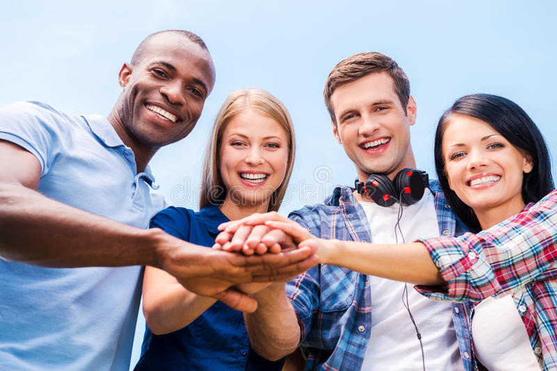 Together we are stronger. Low angle view of four happy young people bonding and holding hands clasped with blue sky in the background stock images