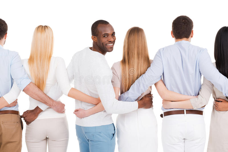 Together we are stronger!. Rear view of group of diverse people bonding to each other and standing against white background while one African men looking over royalty free stock photos