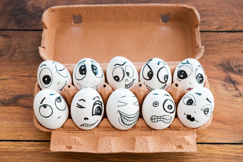 Together we are stronger. Top view of funny eggs with different emotions laying in container on the wooden desk royalty free stock photography