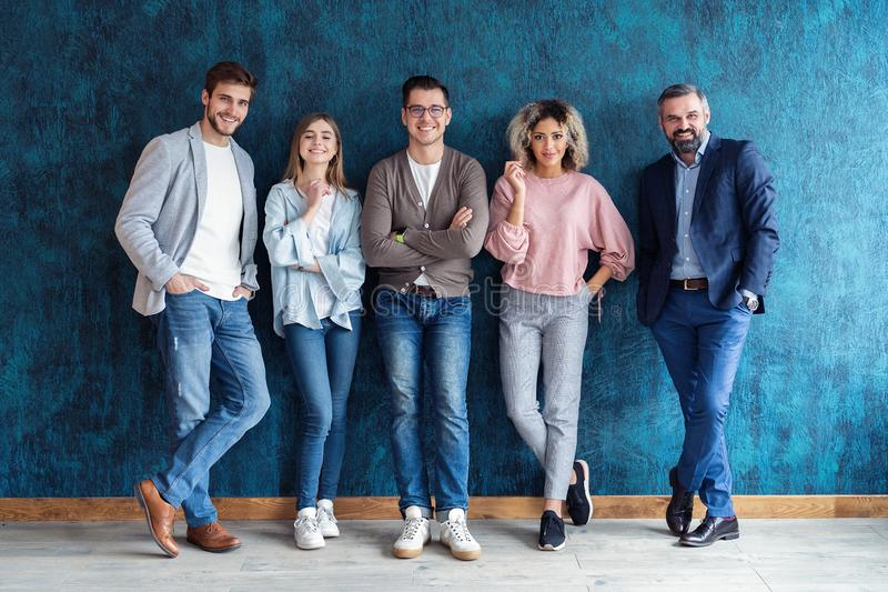 Portrait of creative business team standing together and laughing. Multiracial business people together at startup royalty free stock image
