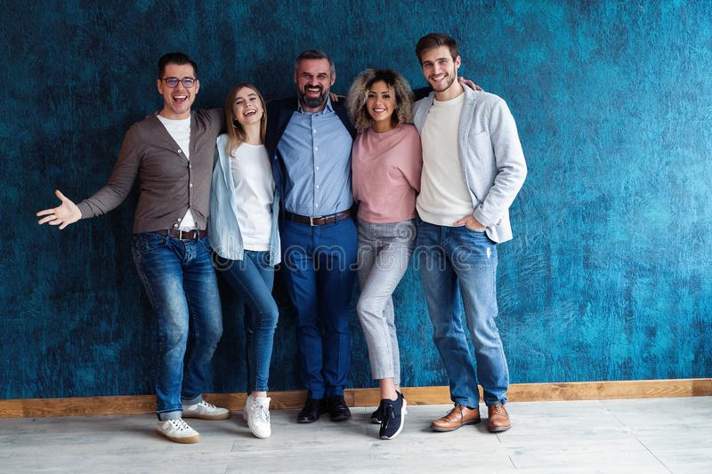 Portrait of creative business team standing together and laughing. Multiracial business people together at startup royalty free stock photography