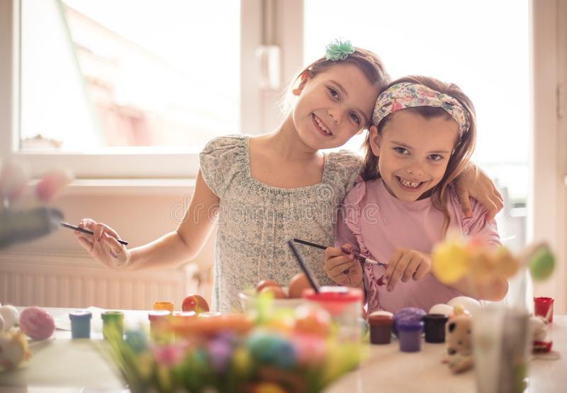 Together we will decorate the Easter. Little girls coloring Easter egg stock photo
