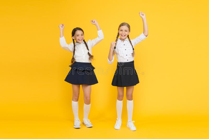Together we are winners. Little schoolchildren making winner gestures on yellow background. Cute small winners enjoying royalty free stock photos