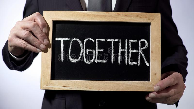 Together written on blackboard, man in black suit holding sign, business concept. Stock footage stock photos