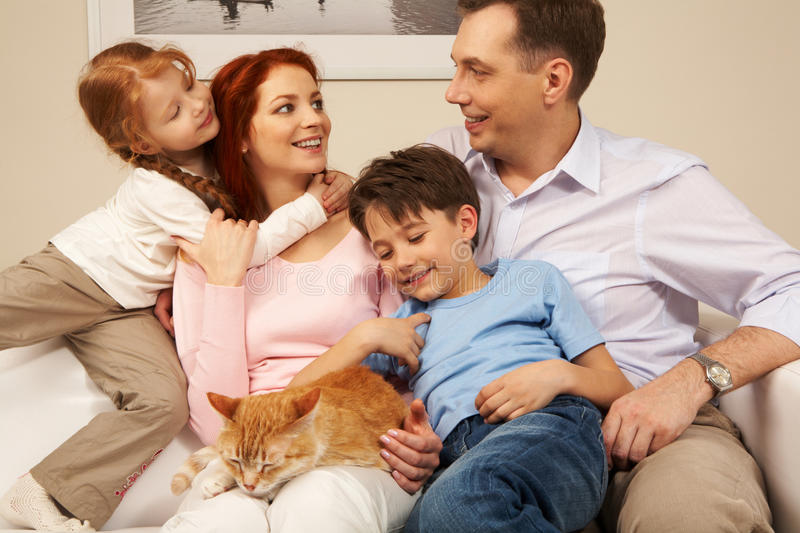 Togetherness. Portrait of affectionate parents and their children enjoying weekend day at home