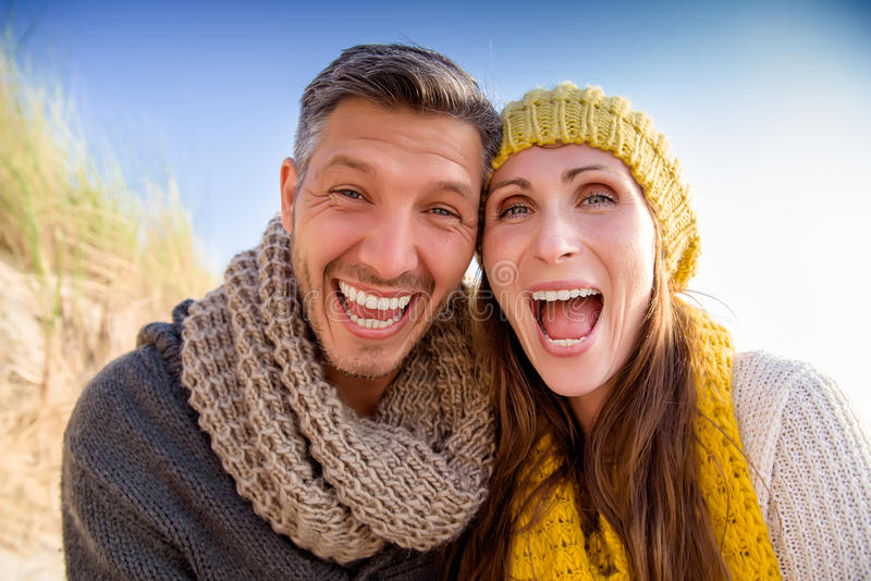 Togetherness in colder season. Happy funny mid adult couple royalty free stock photography