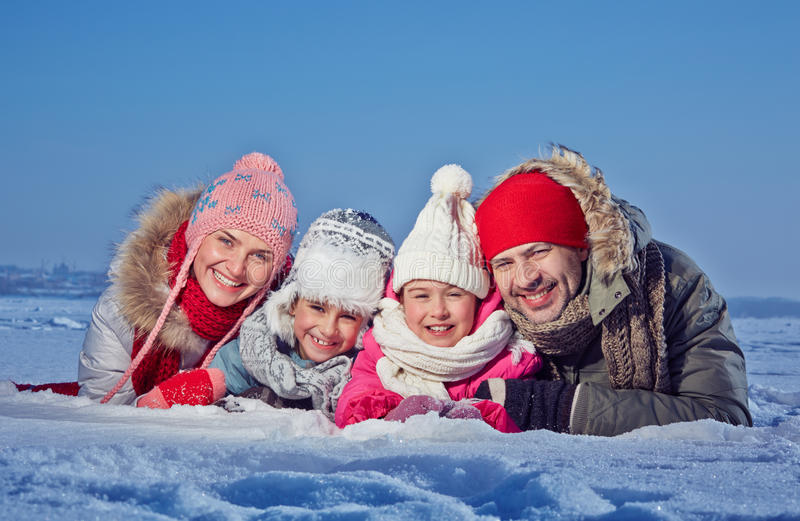 Togetherness. Happy couple and two kids in winterwear lying in snow royalty free stock photos