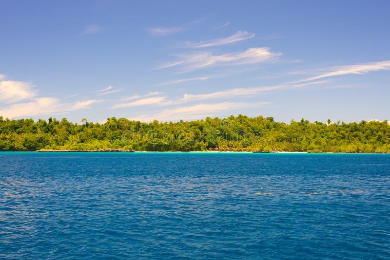Togian öar reser destinationen, Togean öar scenisk strand och kustlinjen med den frodiga gröna djungeln i turkoshavet, Sulawesi,  fotografering för bildbyråer